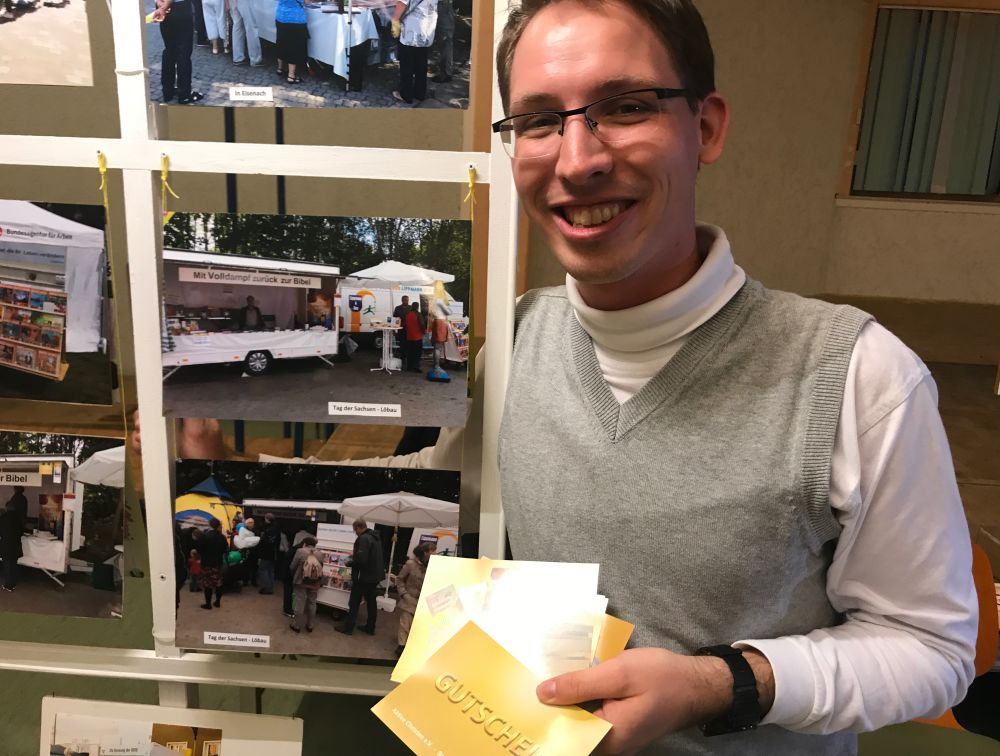 University student Samuel Naumann showing gift cards for free books beside a photo display of the book booths that his family manages in Germany. (Andrew McChesney / Adventist Mission)