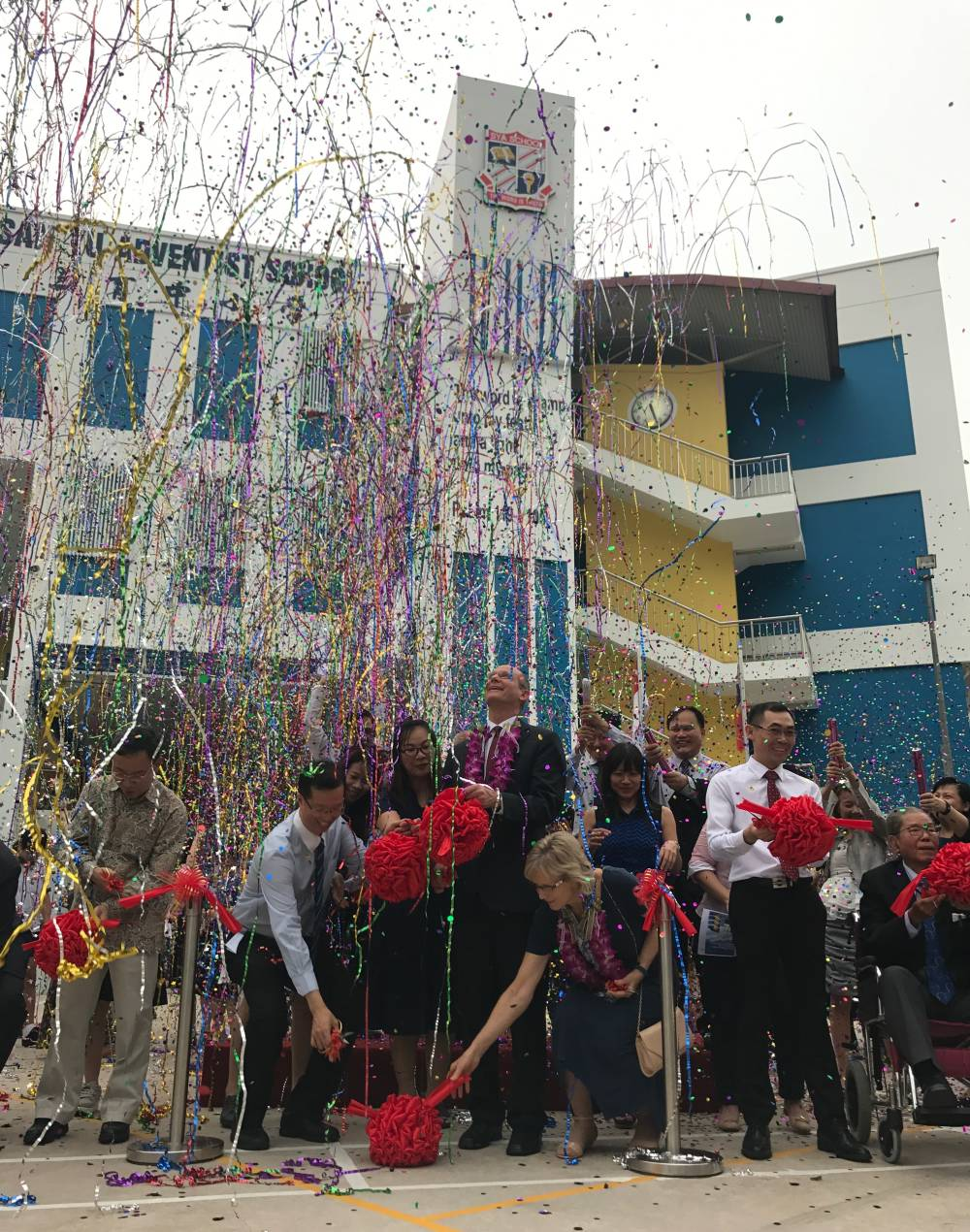 Streamers and confetti filling the air at the rededication ceremony of San Yu Adventist School in Singapore. (Andrew McChesney / Adventist Mission)