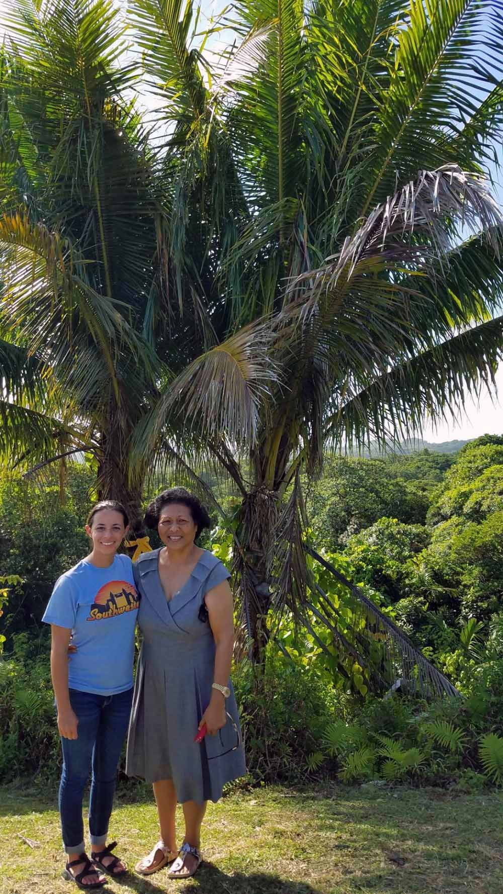 Melissa and Queen Bilung Gloria Salii standing near the two palm trees that the queen planted at the spot where Melissa was rescued at the age of 10.