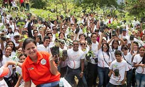 "Hundreds of Seventh-day Adventists hold out small trees before planting some 270 trees in during the church's ""Planting Hope"" program to beautify Venezuela's parks."