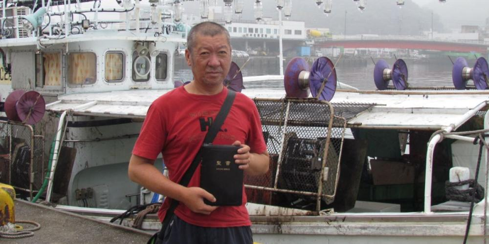 I first met Kojima Sadayuki, pictured holding his Bible at a seaport, when he asked me for a cigarette in a parking lot on the Japanese island of Tsushima. (Photos courtesy of Kurihara Kimiyoshi)