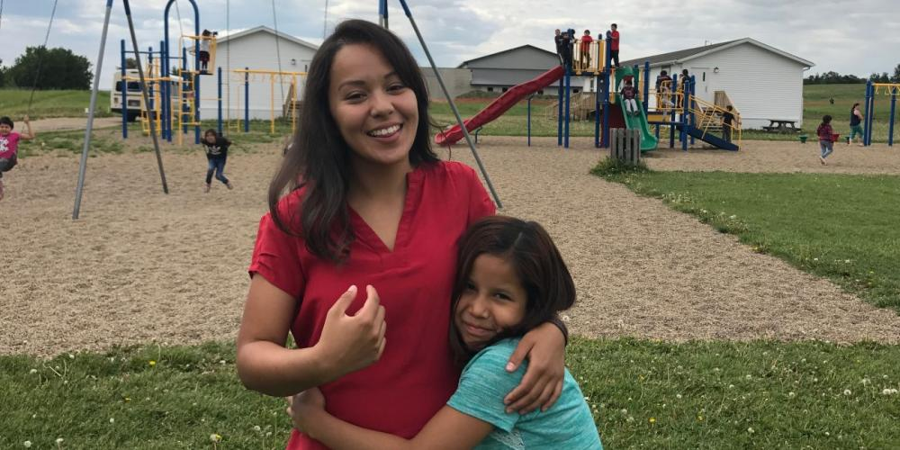 Angelica Cornejo, 22, being embraced by a student on the playground of Mamawi Atosketan Native School in the Canadian province of Alberta. (Andrew McChesney / Adventist Mission)