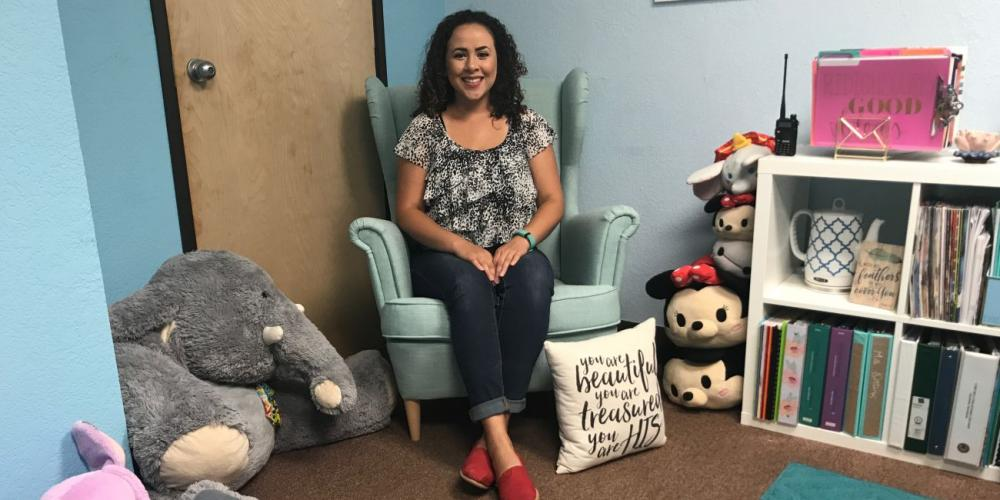 Giselle Ortiz, case manager at Holbrook Indian School, posing in the chair in her office where students usually sit. (Andrew McChesney / Adventist Mission)