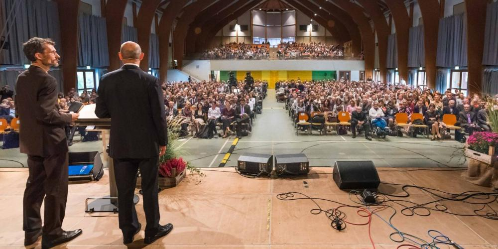Adventist Church leader Ted N.C. Wilson, right, addressing the Adventist Theological Society youth convocation near Hanover, Germany, on Oct. 21, 2017, as Johannes Kolletzki interprets into German. (AYC: ATS Youth Congress / Facebook)