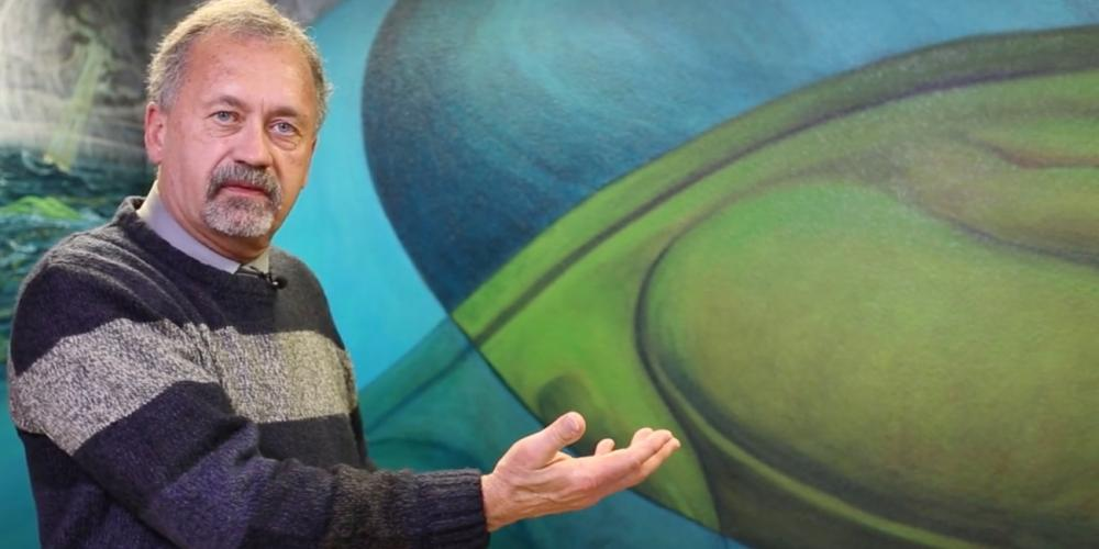 Stan Hudson, 65, gesturing near a mural painted by his former roommate, David L. Friend, at the Creation Study Center in Ridgefield, Washington. (NPUC)