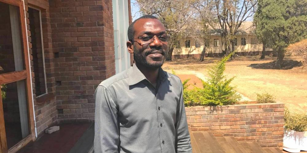 Angolan theology student Paulo Pinto standing outside the main administration building at Solusi University in Zimbabwe. (Andrew McChesney / Adventist Mission)