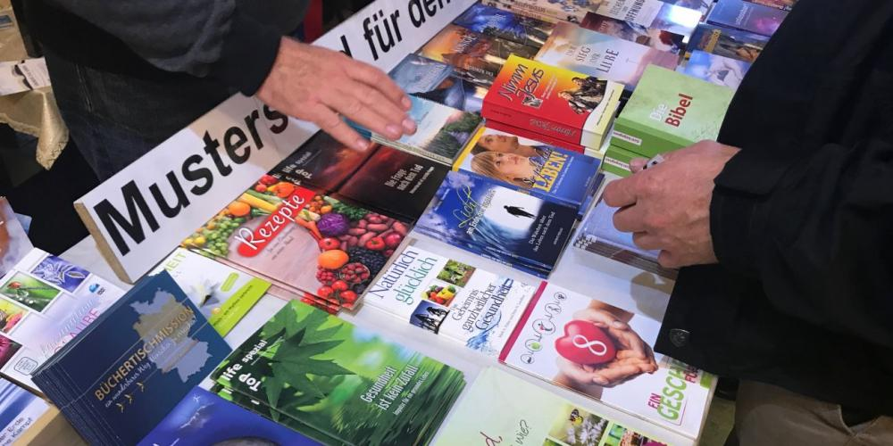A man, right, browsing Adventist literature at the Naumann family book booth at an Adventist Theological Society youth convocation near Hanover, Germany, in October 2017. (Andrew McChesney / Adventist Mission)
