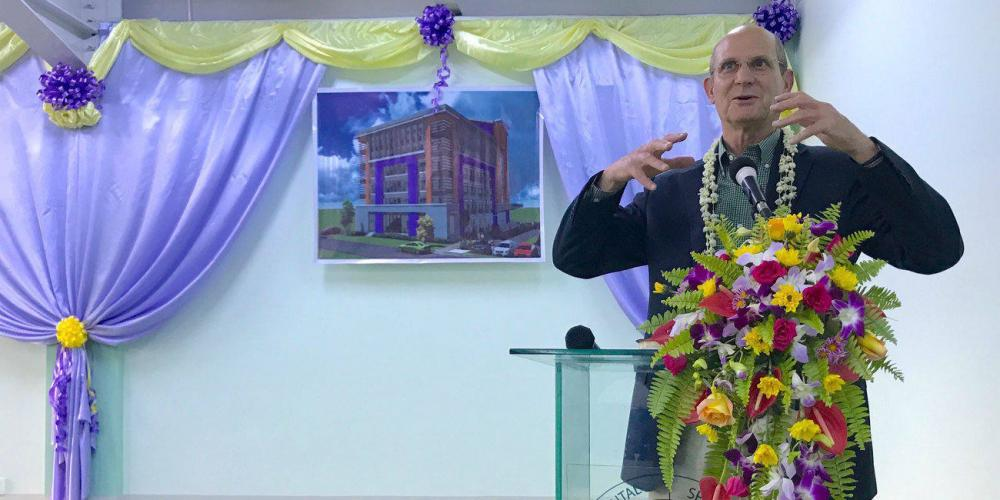 Ted N.C. Wilson, president of the Adventist world church, speaking at the dedication of a new school building in Yangon, Myanmar, on Nov. 9, 2017. A picture of the completed building is hanging on the wall. (Andrew McChesney / Adventist Mission)