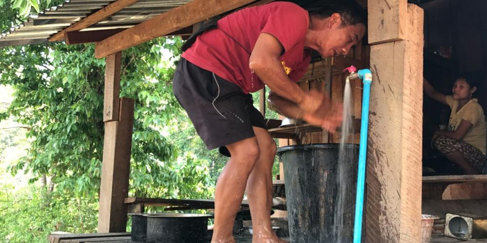 A villager rinsing with water from the new faucet attached to the student missionary-provided water pipeline in Myanmar. (All photos: Tranqui Vergara)