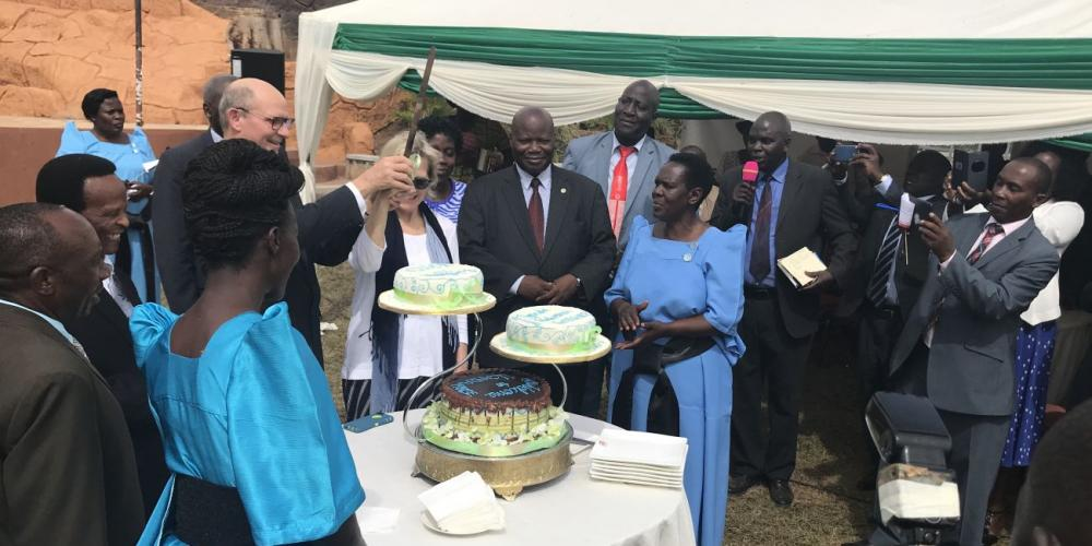 Adventist Church president Ted Wilson holding a knife high to cut cakes at a welcome reception on the grounds of Peniel Beach Hotel in Kampala, Uganda, on Feb. 14, 2018.  Local church leaders asked him to hold the knife like a sword. (Andrew McChesney / Adventist Mission)