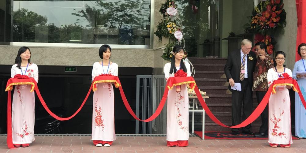 Jannie Bekker, in striped tie, who played a key role in the opening of the Forward Venture community center, speaking with Samuel Saw, president of the Southern Asia-Pacific Division, at an inauguration ceremony in Hanoi, Vietnam, on May 22, 2018. Women wearing traditional Vietnamese costumes are holding a red ribbon to be cut by church leaders. (All photos: Andrew McChesney / Adventist Mission)