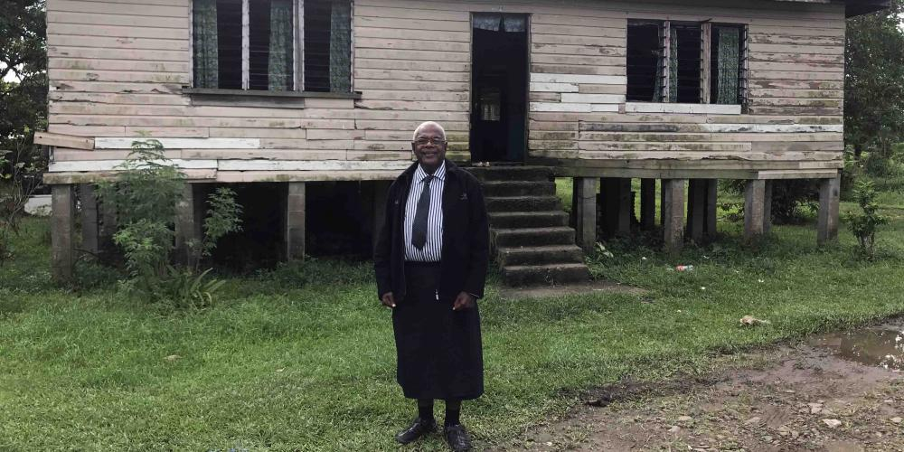 Joeli Rabo, 67, standing outside a typical home in the area of rural Fiji where he is planting his third church. (Andrew McChesney / Adventist Mission)