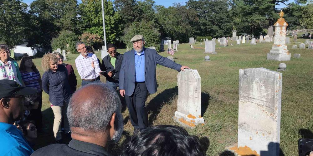 James Nix, center, director of the Ellen G. White Estate, showing George Cobb's tombstone to a General Conference tour group in a cemetery in Brunswick, Maine, on Sept. 13, 2018. (Clinton Wahlen)