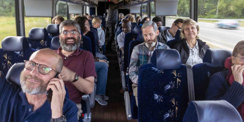 General Conference leaders, including president Ted Wilson, left, and assistant to the president Magdiel Perez Schulz, second left, traveling on a bus during a church heritage tour in the U.S. Northeast on Sept. 11, 2018. (Andrew McChesney / Adventist Mission)