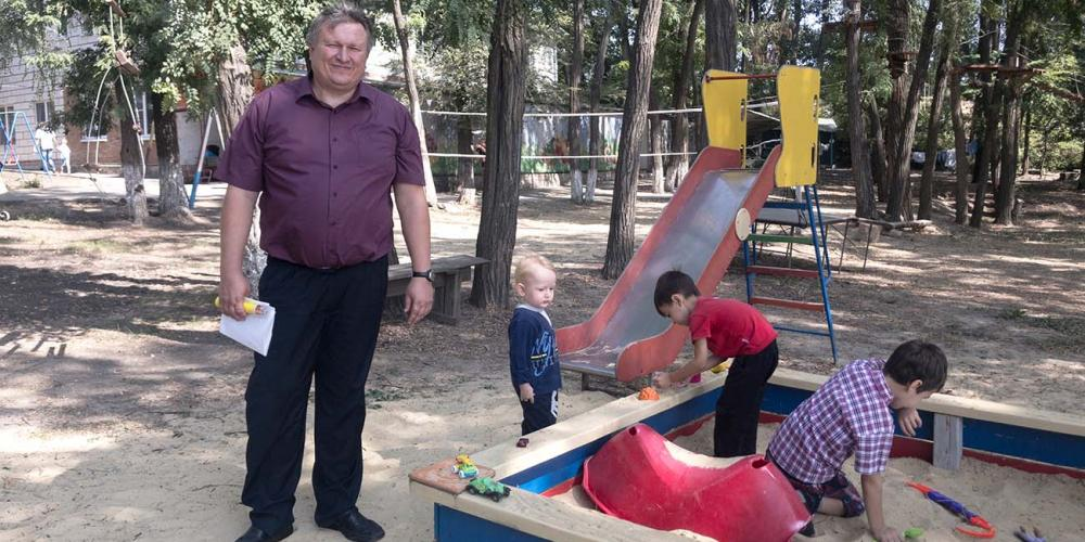 Andrey Prokopev, 43, watching his blond son play with other children in a sandbox at a summer camp in southern Russia. (Andrew McChesney / Adventist Mission)