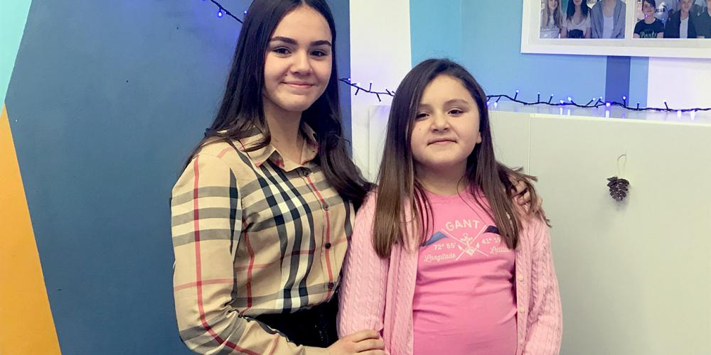 Yana Stoyka, 14, left, standing in her school classroom with her younger sister, Esther, in Prague, Czech Republic. (Andrew McChesney / Adventist Mission)