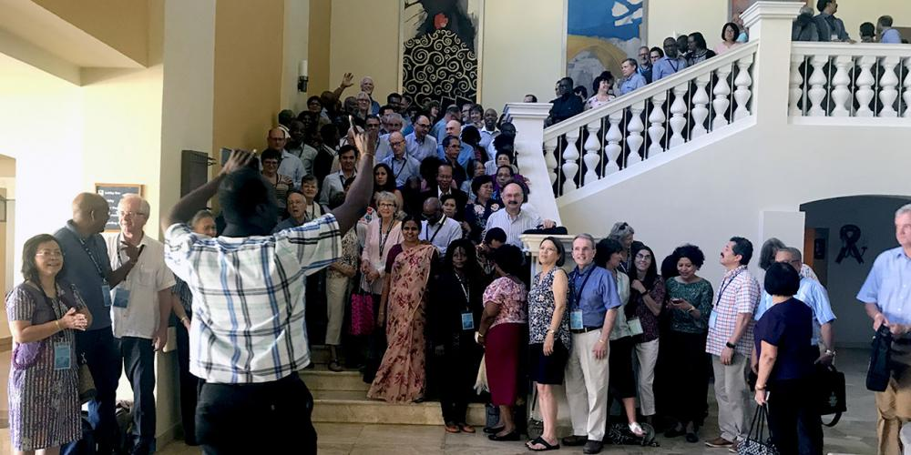 Attendees of the 12th Global Leadership Summit preparing to take a group photo on the stairs of a hotel in Montego Bay, Jamaica, on Feb. 6, 2019. (Andrew McChesney / Adventist Mission)