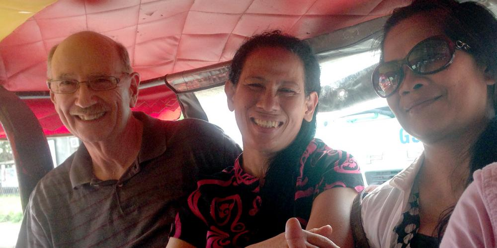 Steven Dragoo with his wife, Dorcas, center, traveling by taxi in the Philippines. (For Adventist Mission)