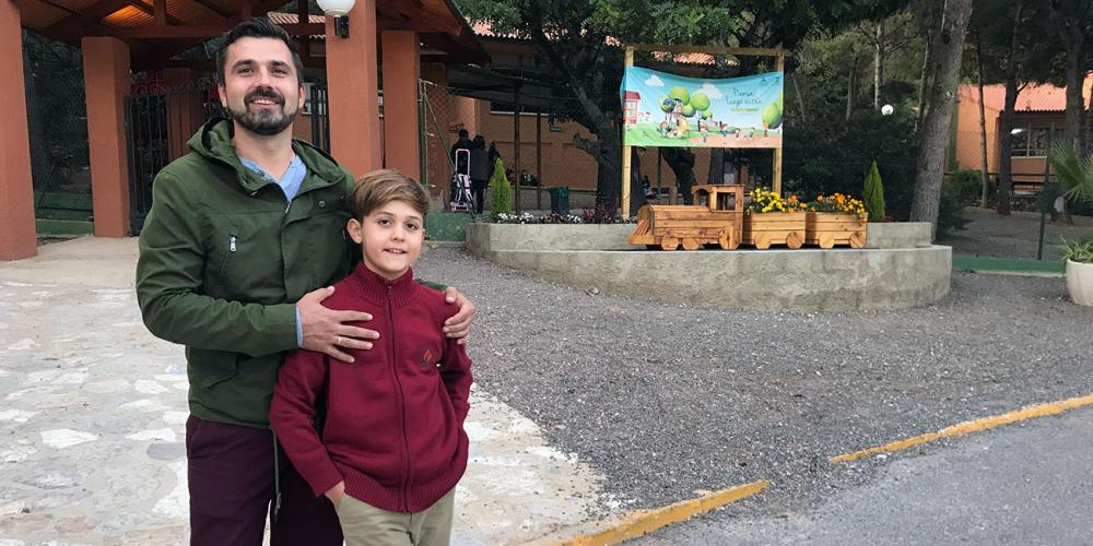 David Lucas Dolete Druga, 10, standing with his father, Laurentiu Stefan Druga, at the gate to the elementary school at Sagunto Adventist College in Sagunto, Spain. (Andrew McChesney / Adventist Mission)
