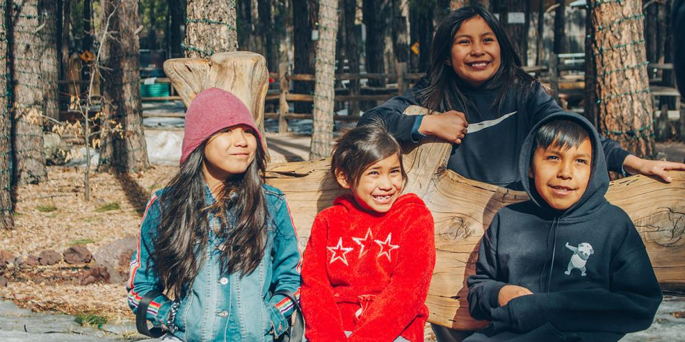 Kallie, 9, in red jacket, enjoying a light moment with her older sister, Katelyn, 11, standing, and several other students at Holbrook Seventh-day Adventist Indian School in Holbrook, Arizona. Their smiles caught the attention of neighbors in their hometown, Chinle. Courtesy of Holbrook Seventh-day Adventist Indian School